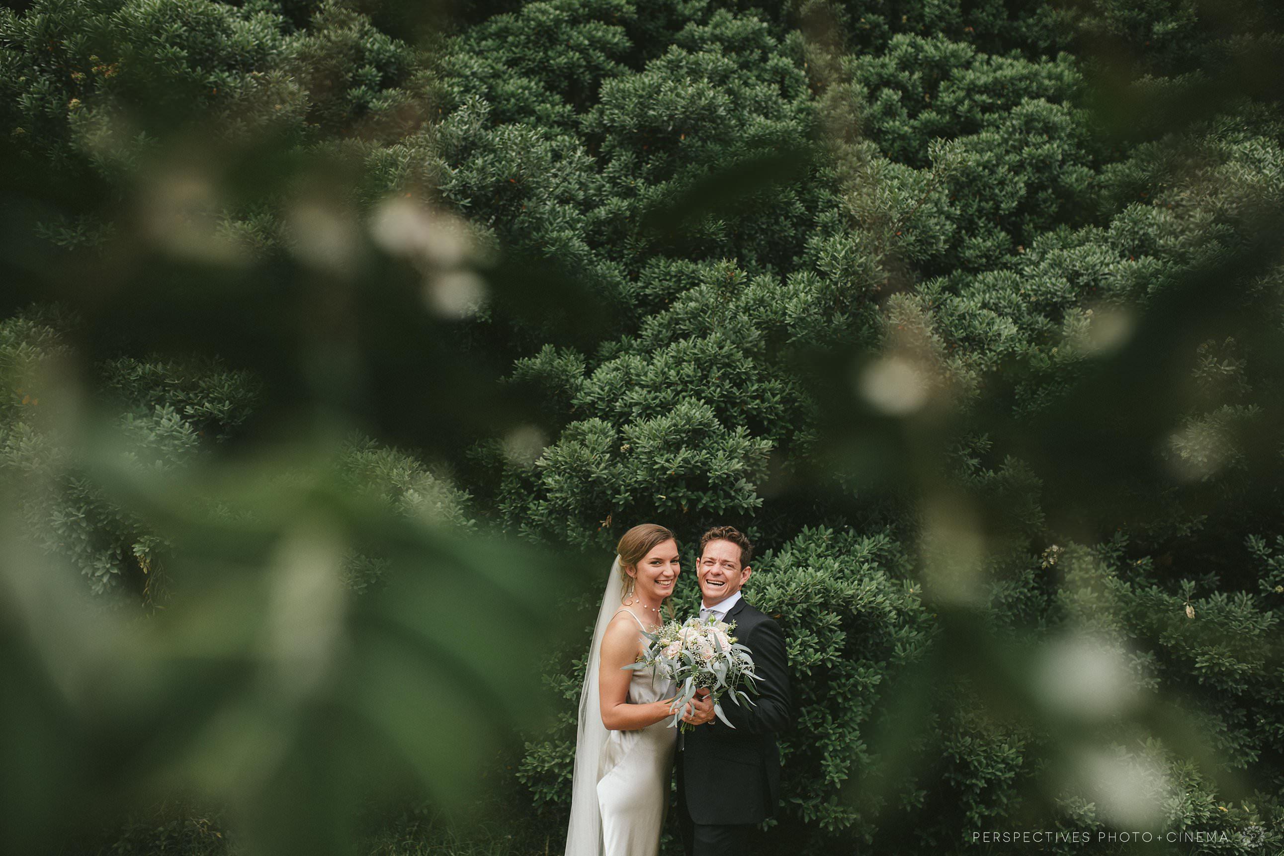 Wedding photo bride & groom under Pohutakawa tree Piha