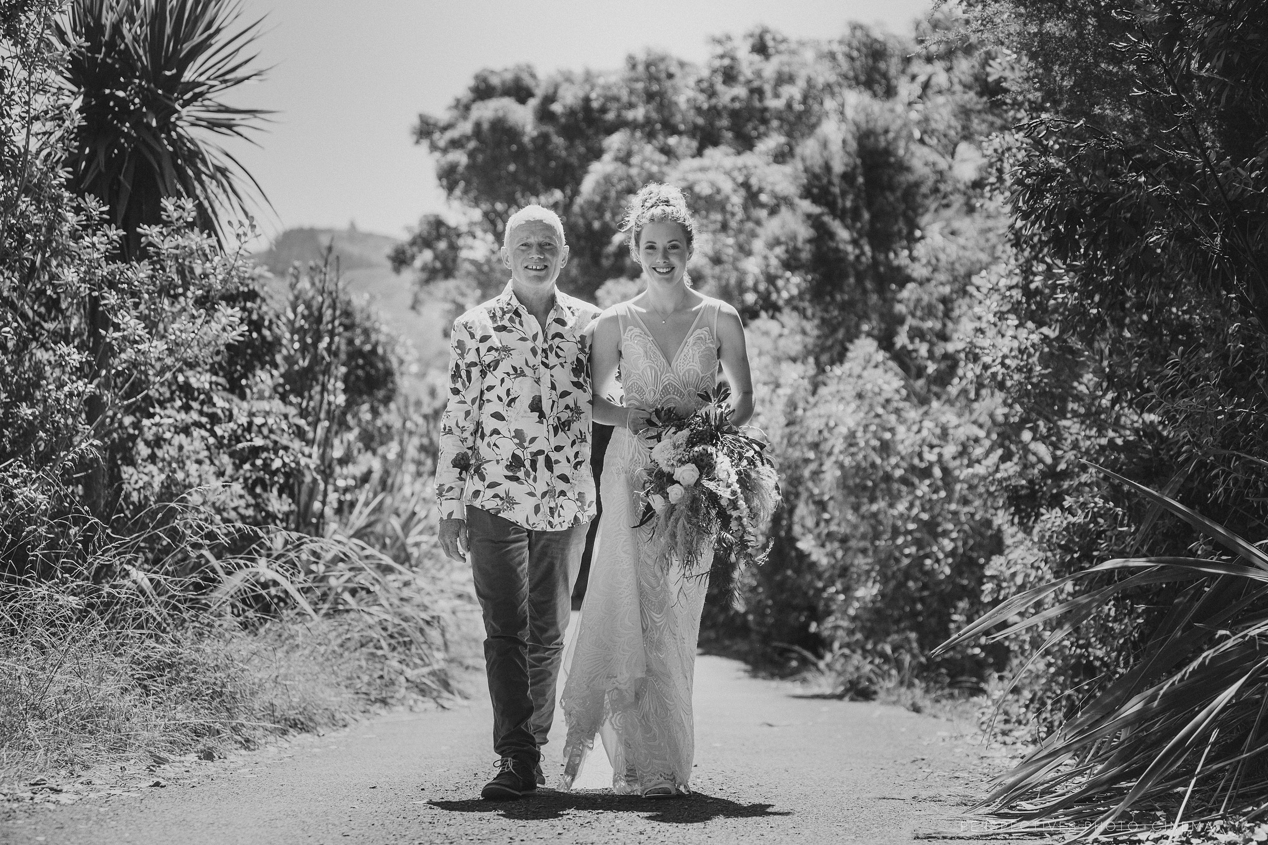 bride and father walking to ceremony in black & white