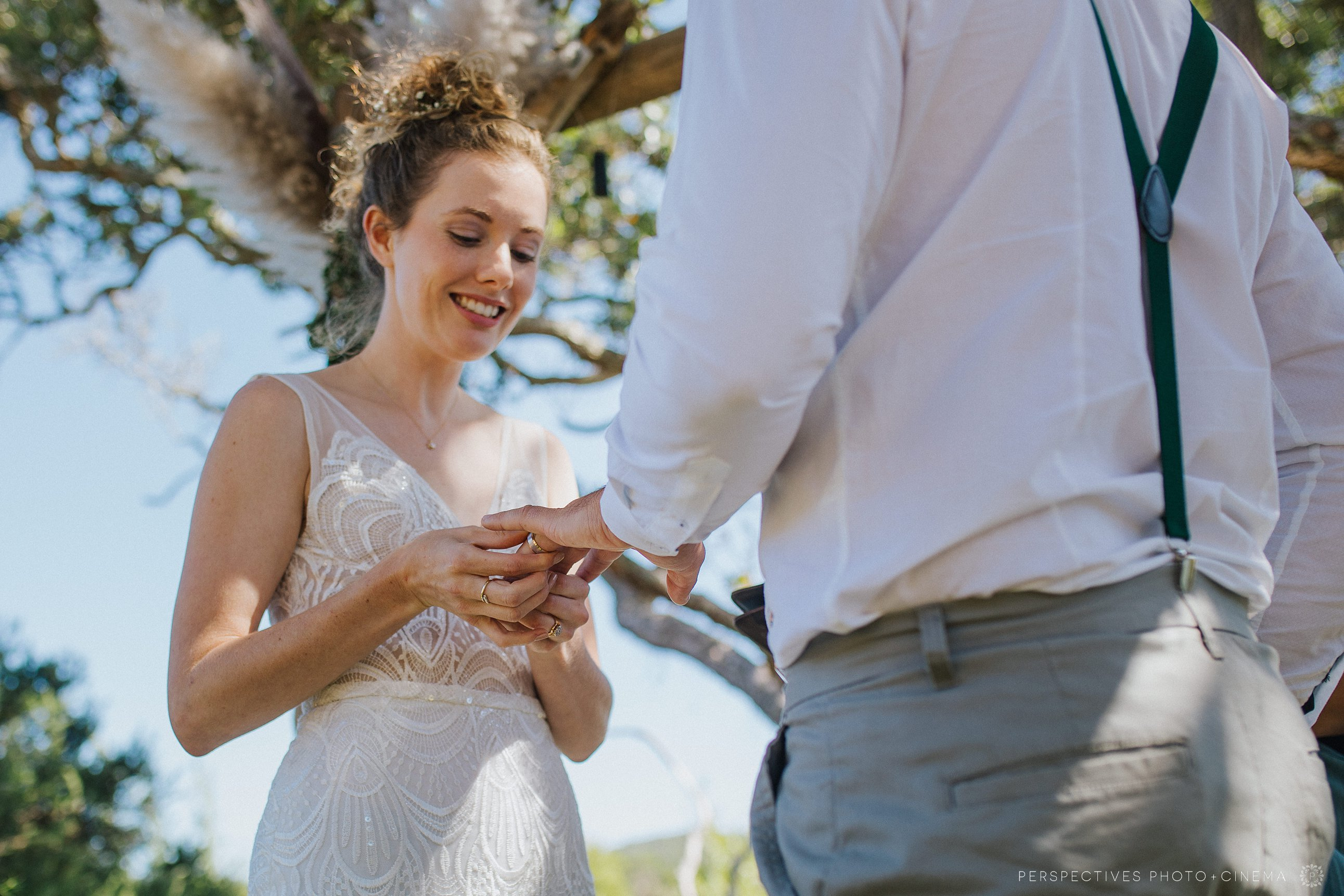 Bride putting on groom's ring in Coromandel wedding ceremony