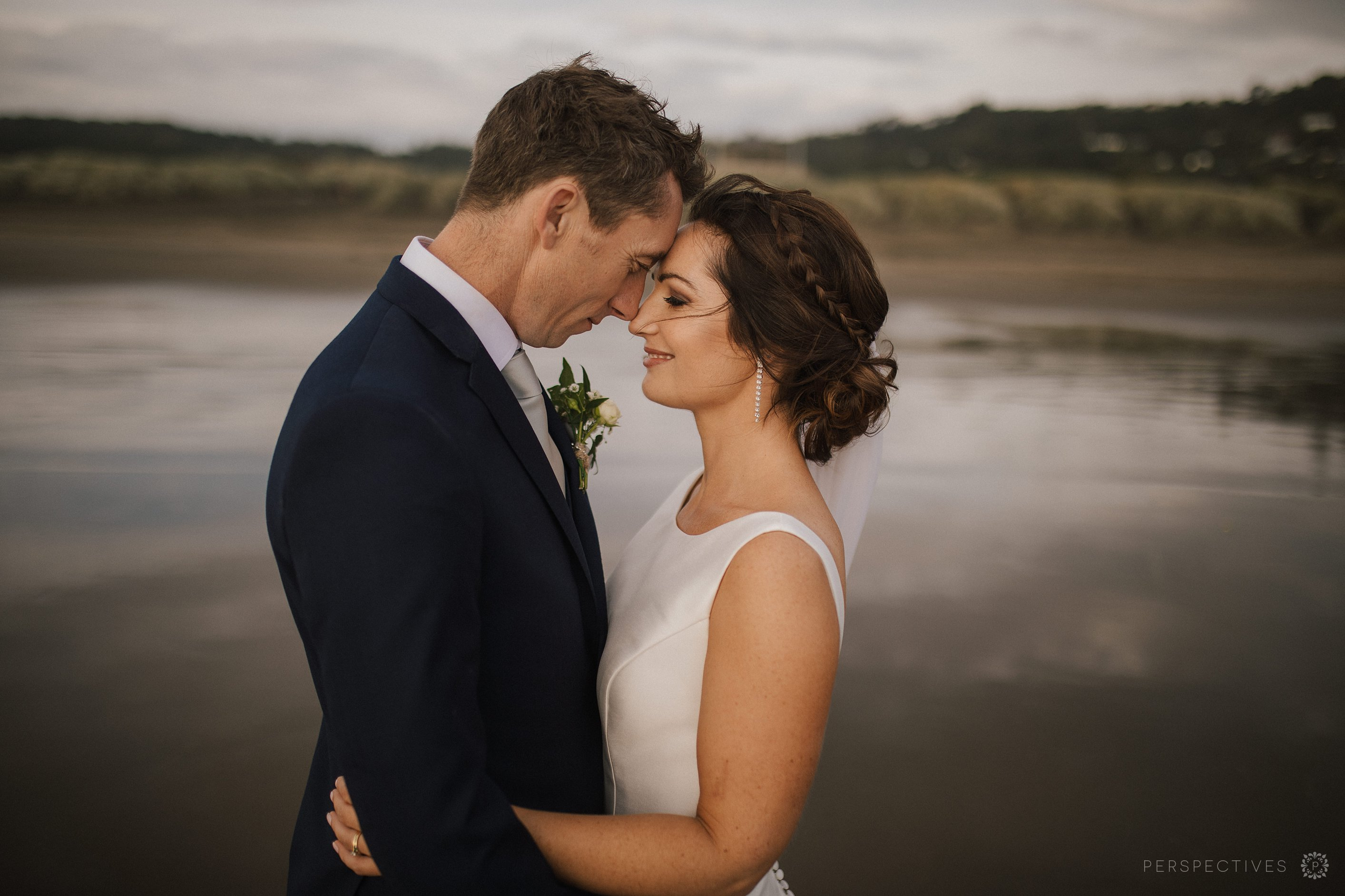 Muriwai beach wedding photos on sand with reflection