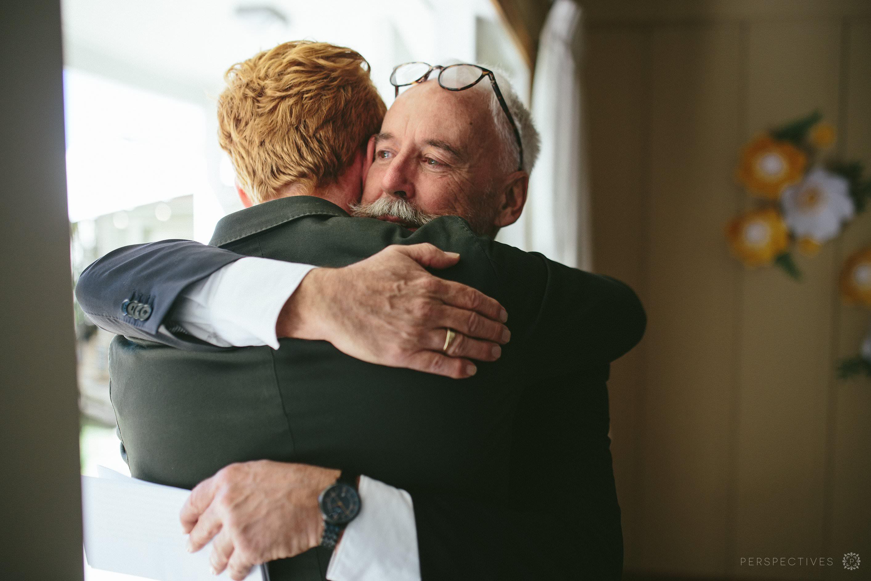 Groom hugging Dad Auckland wedding photographer