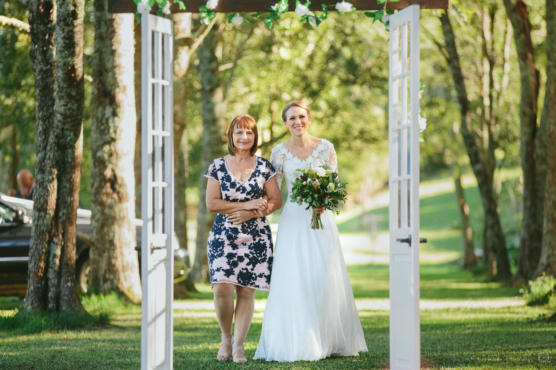 Bride entering wedding ceremony through doorframe
