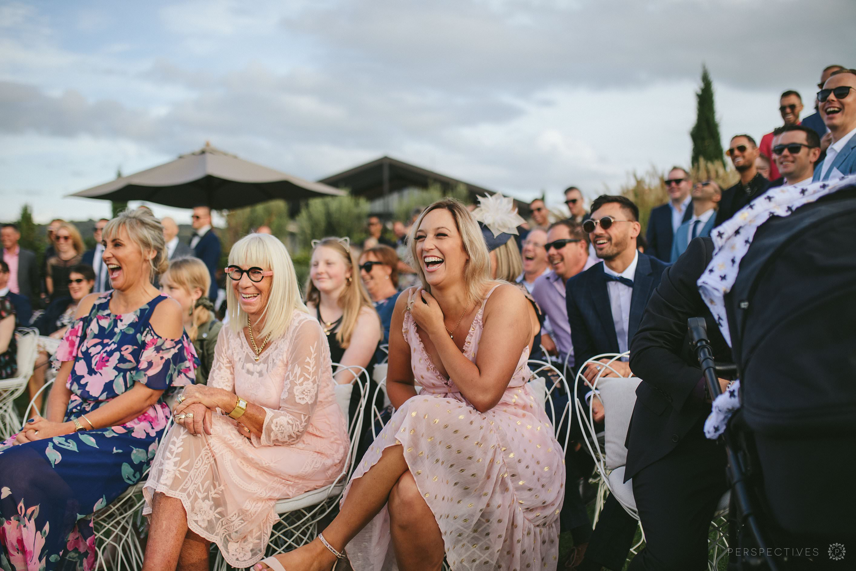 Tantalus Waiheke wedding venue ceremony on lawn guests laughing